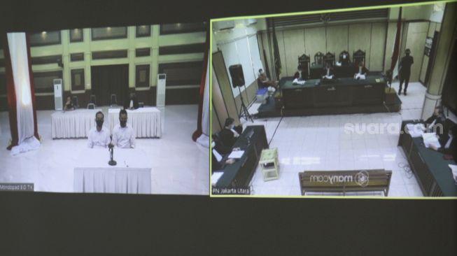 Terdakwa kasus penyiraman air keras terhadap peyidik senior KPK Novel Baswedan, Ronny Bugis (kiri) dan Rahmat Kadir Mahulette (kanan) mengikuti sidang tuntutan secara virtual di Pengadilan Negeri Jakarta Utara, Kamis 11 Juni 2020. [Suara.com/Angga Budhiyanto]