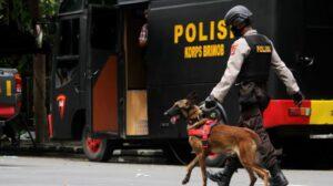 Anggota polisi berjalan dengan anjing pelacak saat mengumpulkan sisa serpihan ledakan bom bunuh diri di depan Gereja Katedral Makassar, Sulawesi Selatan, Senin (29/3/2021). ANTARA FOTO/Arnas Padda