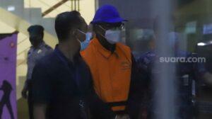Gubernur Sulawesi Selatan, Nurdin Abdullah berjalan dengan mengenakan rompi orange setelah menjalani pemeriksaan di Gedung KPK, Jakarta Selatan, Minggu (28/2/2021). [Suara.com/Alfian Winanto]