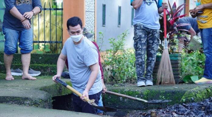 Bupati Kabupaten Pangkep Muhammad Yusran Lalogau, membersihkan selokan dari sampah plastik.(Pangkep.terkini.id).